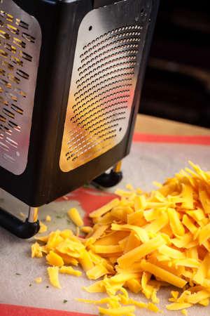 queso cheddar: Queso rallado cheddar amarillo sentado en la tabla de cortar al lado rallador grande