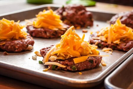 all american burger: Shredded cheddar cheese sitting on raw gourmet hamburgers, on silver plan waiting to be cooked