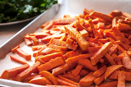 Large pan of fresh cooked sweet potato french fries, fresh out of frying oil Stock Photo