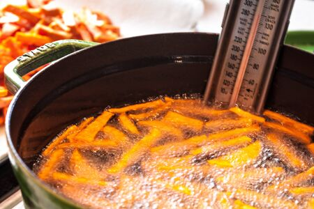 fryer: Fresh sweet potato french fried cooking in pot of hot vegetable oil