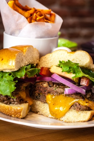 all american burger: Gourmet hamburger with toppings on bun with side of sweet potato french fries