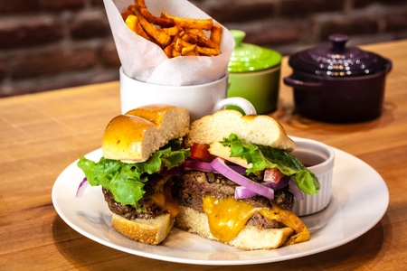 all american burger: White plate with gourmet hamburger with toppings on bun with side of sweet potato french fries