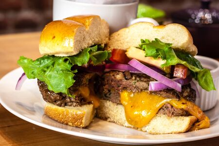 all american burger: Closeup of gourmet hamburger with melted cheese and toppings on bun with side of sweet potato french fries Stock Photo