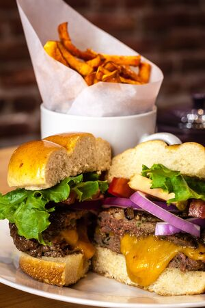 all american burger: Gourmet cheeseburger with toppings on bun with side of sweet potato french fries on white plate