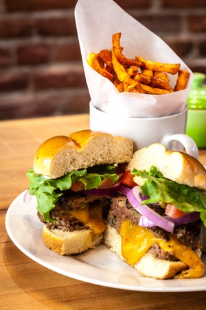 all american burger: Plate with gourmet hamburger with melted cheese on white plate with a side of sweet potato french fries