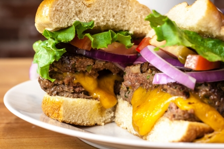 all american burger: Close up of gourmet cheeseburger with melted cheese, tomatoes, lettuce and onions sitting on white plate Stock Photo