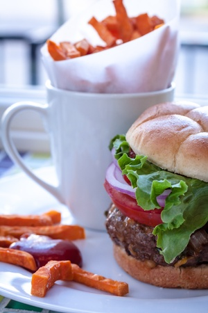 all american burger: Close up of gourmet hamburger with tomato, lettuce and onion toppings on bun with side of sweet potato fries and ketchup Stock Photo