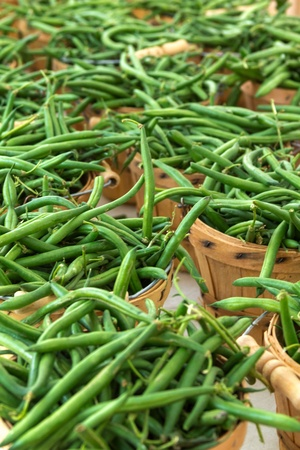 snap bean: Brown bushel baskets full of organically grown green beans for sale at local farmers market Stock Photo