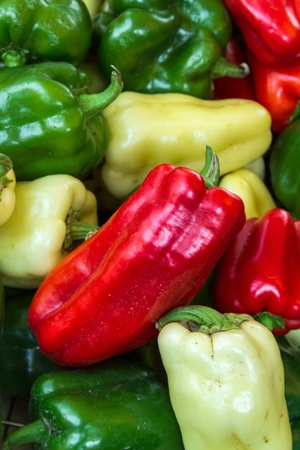 organically: Organically grown red, green and yellow peppers on display in baskets at local farmer market Stock Photo