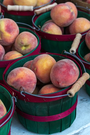Fresh Peaches in green and red bushel basket on display at local farmers market photo