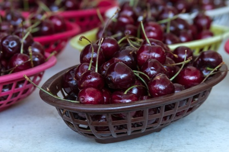 organically: Organically grown red cherries on display in baskets at local farmer market Stock Photo