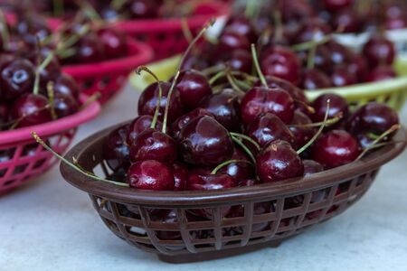 bing: Fresh locally grown red bing cherries in colorful baskets on display at local farmers market Stock Photo