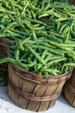 snap bean: Fresh locally grown green beans in brown bushel baskets on display at local farmers market