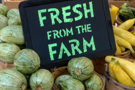 locally: Table filled with locally grown vegetables for sale at farmers market with chalkboard sign Stock Photo