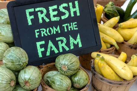 Fresh from the Farm sign on table full of vegetables in baskets on display at local farmers market Stock Photo
