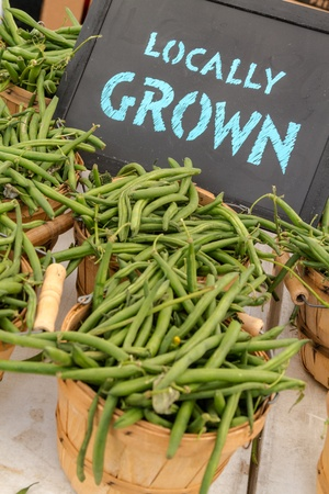 full grown: Locally grown chalkboard sign on table with baskets full of green beans for sale at local farmers market