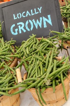 green beans: Cestos llenos de jud�as verdes cultivados en la zona para la venta en el mercado de los agricultores con signo pizarra Foto de archivo