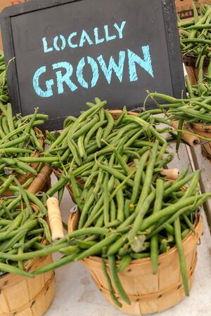 organically: Organically grown green beans for sale at local farmer market with chalkboard sign