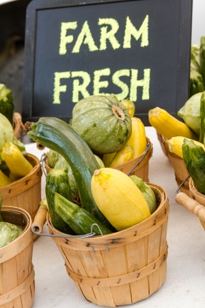 bushel: Bushel baskets full of locally vegetables for sale at farmers market with chalkboard sign Stock Photo