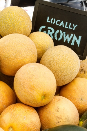 locally: Locally grown cantaloupe melons for sale at local farmers market with handwritten chalk board sign Stock Photo