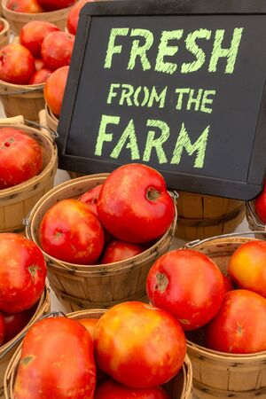 organically: Organically grown red tomatoes in baskets for sale at local farmer market with chalkboard sign