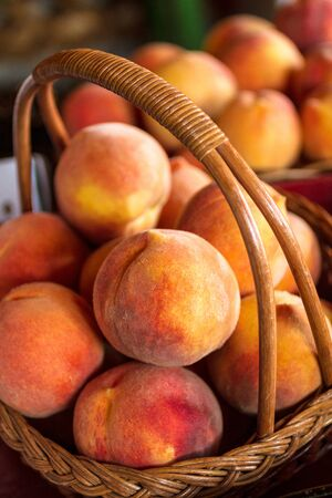 country store: Large ripe yellow peaches in wicker basket for sale in country store