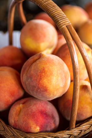 country store: Wicker basket full of ripe yellow peaches in country store Stock Photo