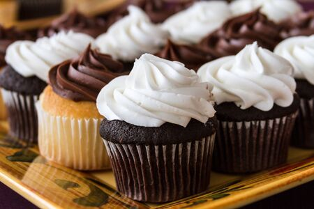 Close up of chocolate and vanilla cupcakes on decorated serving platter