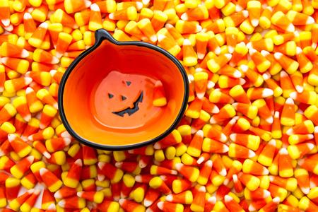 candy corn: Jack-o-lantern bowl sitting on candy corn background