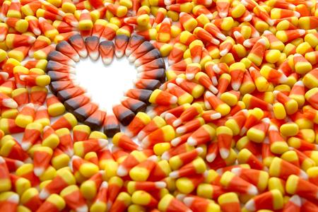 Indian corn arranged in heart shape among candy corn photo