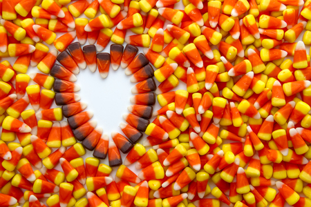 Indian corn heart on candy corn background photo