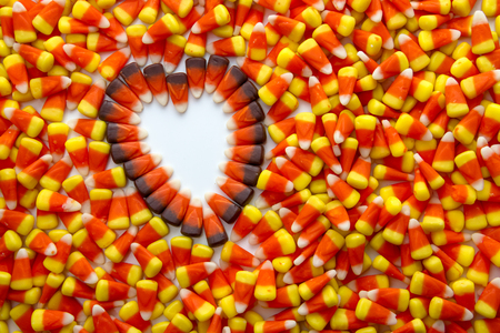 Indian corn heart on candy corn candies background photo