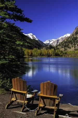2 Adirondack Chairs sitting by blue mountain lake