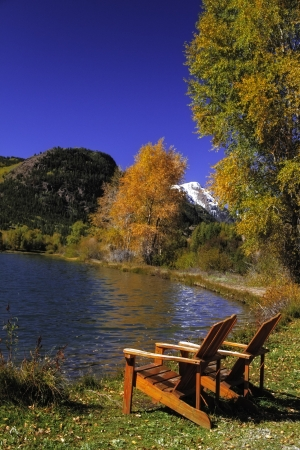 Wooden Adirondack Chairs sitting my mountain lake on autumn day