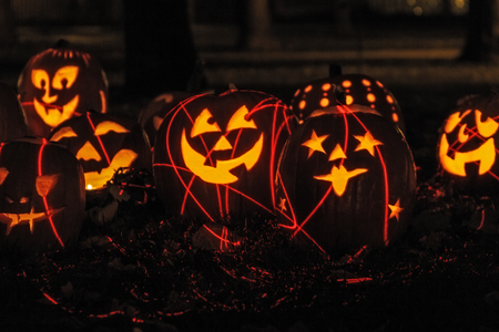 laser lights: Group of candle lit carved Halloween pumpkins sitting in the leaves with red laser lights