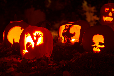 Candle lit Halloween pumpkins sitting on fallen leaves Stock Photo