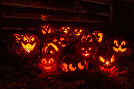Candle lit Halloween pumpkins sitting on fallen leaves in front of old barn