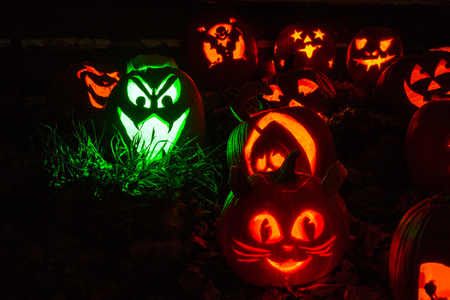 Carved Halloween pumpkins lit with candles sitting in front of old barn lit and one lit with green light