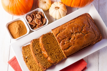 Loaf of pecan pumpkin bread sitting on white plate with orange napkin, spices and assorted pumpkins