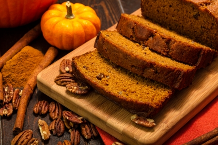 Pumpkin bread loaf sitting on wooden cutting board with pecan nuts and cinnamon spices