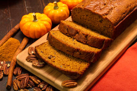 Festive setting of sliced pumpkin loaf sitting on wooden cutting board with orange cloth napkin, cinnamon sticks and pecan nuts photo