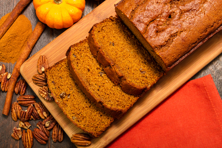 Sliced pumpkin bread loaf sitting on wooden cutting board with pecan nuts and cinnamon spices photo