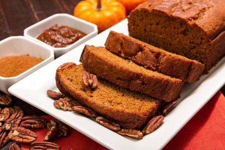Festive holiday table with sliced loaf of pumpkin bread sitting on white plate with nuts and pumpkin butter photo
