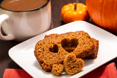 Heart shape stamped into slice of fresh baked pumpkin bread sitting on white plate with large cup of coffee photo