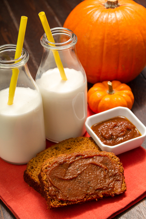 2 glasses of milk with yellow straws sitting on orange napkin with slices of pumpkin bread and small gourds photo