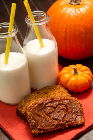 Slices of pumpkin bread with heart shape drawn into pumpkin spread sitting on orange napkin with glasses filled with milk and yellow straws photo