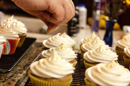 decorating: Hand sprinkling glitter sugar sprinkles onto frosted cupcakes