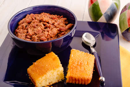cornbread: Bowl of elk meat chili sitting in blue bowl and plate with cornbread