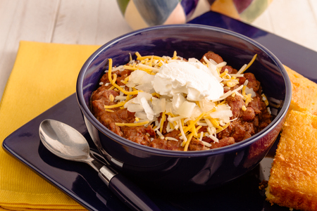 cornbread: Elk meat chili with beans, sour cream, shredded cheese, diced onions in bowl sitting on blue plate with cornbread