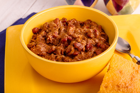 cornbread: Yellow bowl filled with red meat chili with beans and cornbread Stock Photo
